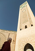 Low angle view of senior man wearing traditional clothing standing nearby Hassan II Mosque, Casablanca, Morocco