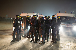 "© Licensed to London News Pictures . 23/10/2016 . Calais , France . Riot police deployed at the Calais migrant camp known as "" The Jungle "" , in Northern France , as residents set fires , on the evening before the start of the eviction and destruction of the camp . Photo credit: Joel Goodman/LNP"