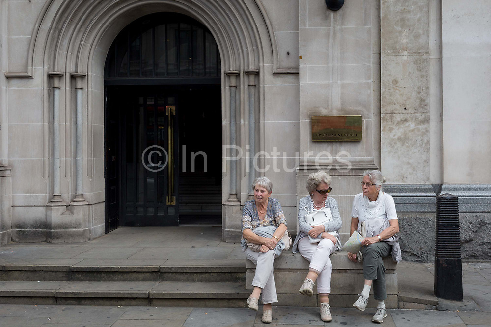 Three elderly ladies rest outside parliamentary offices on Whitehall, on 15th July 2019, in London, England.