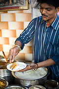 A man makes different kinds of chat (street food snacks) at the Ashok Chat Corner in Chawri Bazaar, Old Delhi India