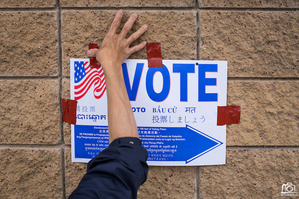 Milpitas resident and Polling Place official My Hoang tapes a sign to a brick wall along Milpitas Blvd. during the California Presidential Election in Milpitas, California, on June 7, 2016. (Stan Olszewski/SOSKIphoto)