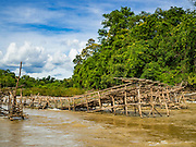 17 JUNE 2016 - DON KHONE, CHAMPASAK, LAOS:  Fish traps in the Mekong River at Khon Pa Soi Waterfalls, on the east side of Don Khon. It's the smaller of the two waterfalls in Don Khon. Fishermen have constructed an elaborate system of rope bridges over the falls they use to get to the fish traps they set. Fishermen in the area are contending with lower yields and smaller fish, threatening their way of life. The Mekong River is one of the most biodiverse and productive rivers on Earth. It is a global hotspot for freshwater fishes: over 1,000 species have been recorded there, second only to the Amazon. The Mekong River is also the most productive inland fishery in the world. The total harvest of fish from the Mekong is approximately 2.5 million metric tons per year. By some estimates the harvest in the Tonle Sap (in Cambodia) had doubled from 1940 to 1995, but the number of people fishing the in the lake has quadrupled, so the harvest per person is cut in half. There is evidence of over fishing in the Mekong - populations of large fish have shrunk and fishermen are bringing in smaller and smaller fish.        PHOTO BY JACK KURTZ