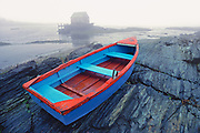 The cold tones of a foggy morning at Nova Scotia's Blue Rocks contrast with the bright red trim on a stranded rowboat. ©Ric Ergenbright