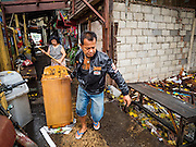 28 SEPTEMBER 2015 - BANGKOK, THAILAND: A worker moves a dresser out of an abandoned home near Wat Kalayanamit. Fifty-four homes around Wat Kalayanamit, a historic Buddhist temple on the Chao Phraya River in the Thonburi section of Bangkok, are being razed and the residents evicted to make way for new development at the temple. The abbot of the temple said he was evicting the residents, who have lived on the temple grounds for generations, because their homes are unsafe and because he wants to improve the temple grounds. The evictions are a part of a Bangkok trend, especially along the Chao Phraya River and BTS light rail lines. Low income people are being evicted from their long time homes to make way for urban renewal.    PHOTO BY JACK KURTZ