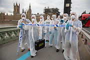 Extinction Rebellion 'crime scene investigators' in white suits and masks walk over Westminster Bridge past the Houses of Parliament with climate crime scene tape to investigate areas of ecocide in a performance outside the Cabinet Office on 7th September 2020 in London, United Kingdom. The 20 investigators were protesting at the UK government's ecocide along the HS2 route. Extinction Rebellion is a climate change group started in 2018 and has gained a huge following of people committed to peaceful protests. These protests are highlighting that the government is not doing enough to avoid catastrophic climate change and to demand the government take radical action to save the planet.