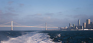 The view of city skyline and old Bay Bridge from a ferry leaving San Francisco on a cold and windy day in July.
