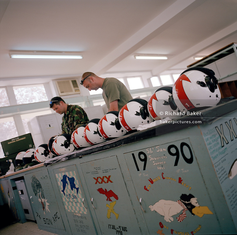 Equipment suppliers check flying pilots' helmets of 'Red Arrows', Britain's Royal Air Force aerobatic team.