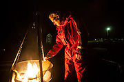 Bjornar Hogset, dressed in his fisherman's survival suit, stokes a campfire outside his home in Sorland, Vaeroy Island, Lofoten Islands, Norway.