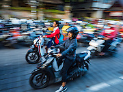11 OCTOBER 2016 - UBUD, BALI, INDONESIA:  A woman passes motorcycle parking on Jalan (Street) Raya Ubud during the morning market. The morning market in Ubud is for produce and meat and serves local people from about 4:30 AM until about 7:30 AM. As the morning progresses the local vendors pack up and leave and vendors selling tourist curios move in. By about 8:30 AM the market is mostly a tourist market selling curios to tourists. Ubud is Bali's art and cultural center.     PHOTO BY JACK KURTZ