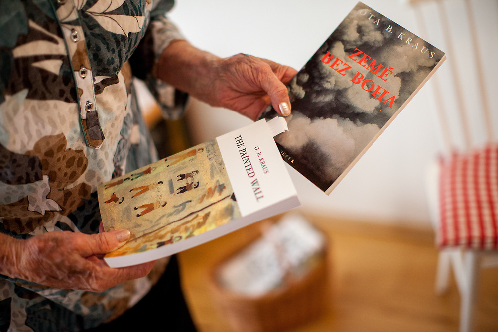 """Dita Kraus holding two books written by her husband Ota B. Kraus in her flat in Prague Vinohrady. Born in Prague to a Jewish family in 1929, Dita Kraus has lived through the most turbulent decades of the twentieth and early twenty-first centuries. Here, Dita writes in her book """"A Delayed Life: The true story of the Librarian of Auschwitz"""" with startling clarity on the horrors and joys of a life delayed by the Holocaust. From her earliest memories and childhood friendships in Prague before the war, to the Nazi-occupation that saw her and her family sent to the Jewish ghetto at Terezín, to the unimaginable fear and bravery of her imprisonment in Auschwitz and Bergen-Belsen, and life after liberation."""