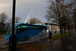 © Licensed to London News Pictures. 30/11/2018. Cardiff, UK.  A pedestrian is splashed by a coach driven through standing water as a rainbow is seen in the sky above the Royal Welsh College of Music and Drama in Cardiff this morning (Friday 30th November 2018) . Photo credit: Joel Goodman/LNP