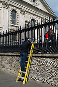 While a workmate manhandles a red panel, a workman pauses up yellow lassers at the rear St. Martin-in-the-Fields church off Trafalgar Square, on 30th April 2019, in London, England.