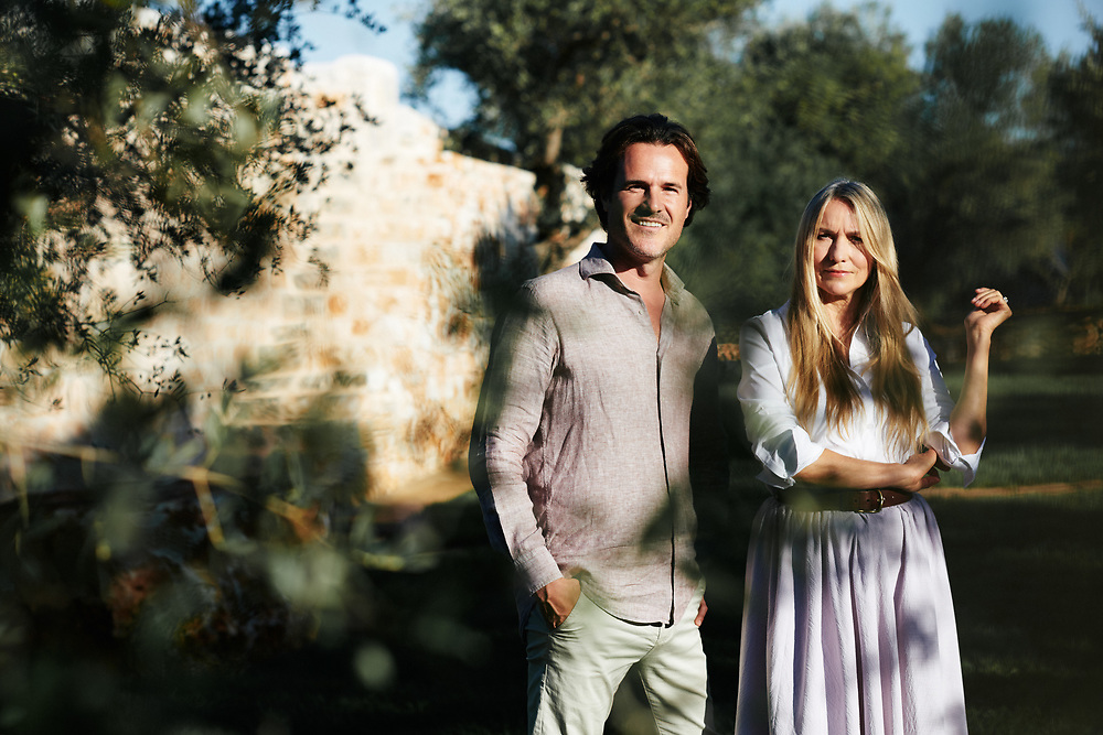 Collette Dinnigan and her husand Bradley Cocks, posing in their villa's garden. Ostuni, Italia. September 28, 2019.