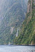 Cruise ship Milford Mariner sailing past Stirling Falls in Milford Sound, Fiordland National Park, New Zealand.