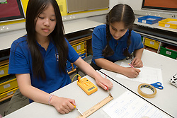 Two secondary school girls measuring resistance in Physics lesson,