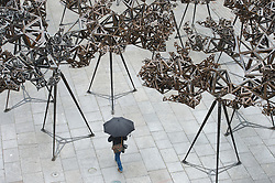 © London News Pictures. 29/05/15. London, UK. A photographer walks under Conrad Shawcross's new installation 'The Dappled Light of the Sun' in the Royal Academy Courtyard, Central London. Photo credit: Laura Lean/LNP