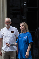 London, UK. 20th July, 2021. A NHSPay15 campaigner prepares to pose outside 10 Downing Street with former Labour Party leader Jeremy Corbyn after presenting a petition signed by over 800,000 people calling for a 15% pay rise for NHS workers. At the time of presentation of the petition, the government was believed to be preparing to offer NHS workers a 3% pay rise in 'recognition of the unique impact of the pandemic on the NHS'.