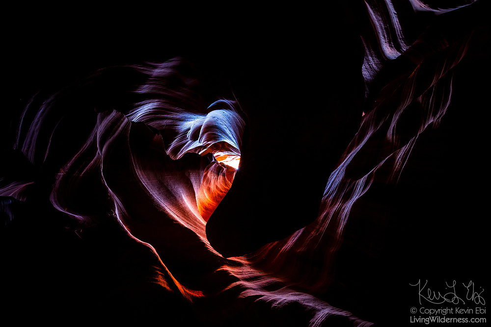 "A heart shape appears among the curves of the ceiling of Upper Antelope Canyon on Navajo land near Page, Arizona. Violent flash floods sculpt the sandstone slot canyon, leaving undulating, layered walls. The Navajo people call the canyon Tsé bighánílíní dóó Hazdistazí, which means ""the place where water runs through rocks."""