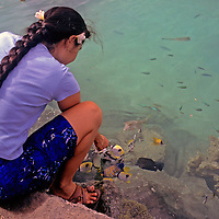 Oceania, South Pacific, French Polynesia, Tahiti. Polynesian woman feeds tropical fish.