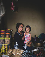 A woman holds a child at the market in Tangkiling, Central Kalimantan, Indonesia