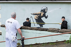 © Licensed to London News Pictures; 10/12/2020; Bristol, UK. People view and take photos of a mural in the style of Banksy showing a woman coughing out her dentures on a wall in Vale Street during the Covid-19 coronavirus pandemic in England. With England under a three-tier system Bristol is in Tier 3. With a roughly 22-degree gradient incline, Vale Street in the Totterdown area of Bristol is said to be England's steepest street. Photo credit: Simon Chapman/LNP.