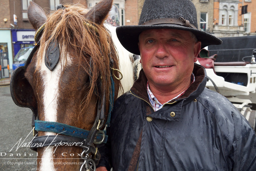 The driver of our horse drawn carriage poses with his horse in the spitting rain, Dublin, Ireland.