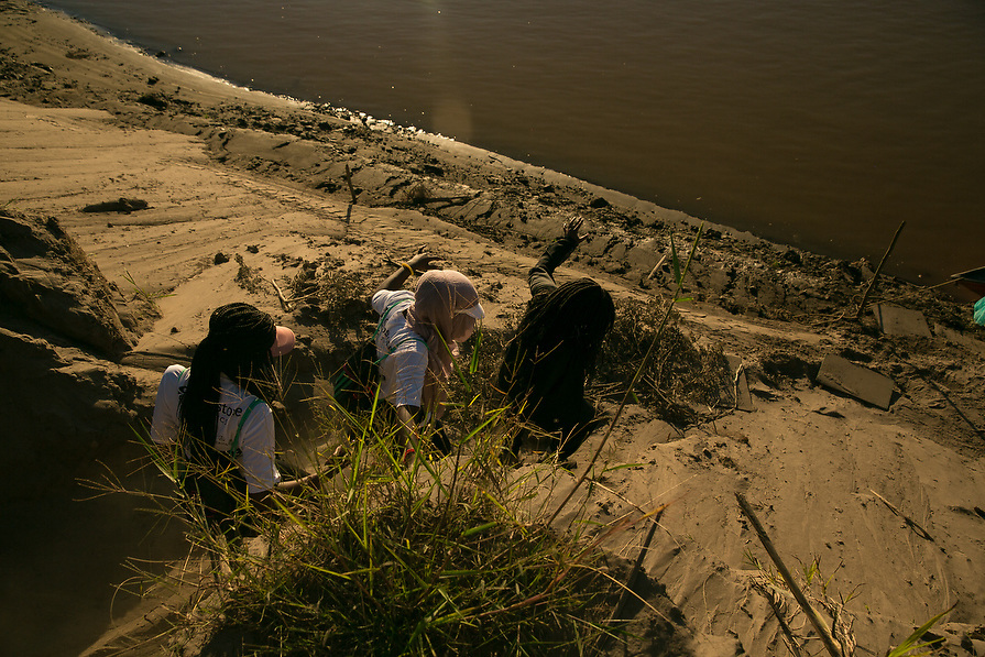 Girls follow each others footsteps as they make their way down to the river.