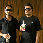 Ricky Puri (left, 25) and Jatin Khosla (20) chilling while having a soft dring they bought at the McDonald fast food chain. West End mall, Ludhiana, Punjab