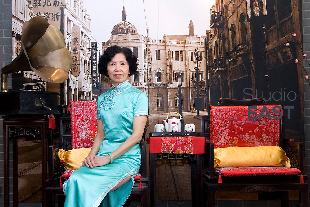 Wang Weiyu poses in a Qipao traditional dress in front of things that evoke Shanghai in the thirties: ancient furniture, an old record player, and an old photo of the town, in Shanghai, China, on April 19, 2010. Photo by Lucas Schifres/Pictobank . Inspired by Wong Kar-Wai's film 'In mood for love', Wang Weiyu, a 62-year-old former Japanese teacher, opened her 'Qipao salon' in 2007. It became famous when a TV show mentioned it. Now about 370 Shanghaiese ladies, mostly senior, come regularly to her Salon to learn how to dance, walk, and sit, wearing the Qipao. This elegant dress, originally worn by Manchus, became the symbol of Shanghai 'Pearl of the Orient', in the thirties. But during the seventies, the Cultural Revolution saw it as decadent and bourgeois, and forbade it. 50-year-old women who couldn't wear it when they were young now come back to the cultural and traditional Qipao. 'When  I wear it, I feel pretty, I am always in a good mood' comments a 47-year-old woman.