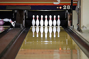 track in a bowling alley with straight up and falling pins