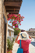 Female tourist photographing flowers on street, Cyprus