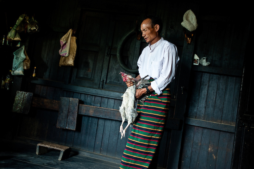 """Yaboh, Chief of Pansar, strangles a chicken before making a ritual sacrifice to the skull behind his home. After he dug the chicken's heart out with his thumb, he turned for the door and said, """"I'm sorry, but no one can watch me feed the skull."""""""