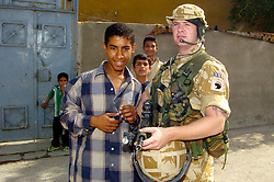 """Pvt Mark """"Bruce"""" Lee 23 from Eckington Sheffield. with local children outside the Alfar Ahidi police station in Basrah"""