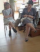 Living History event. Woman sewing watched by young girl. 1940s period.