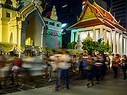 "01 MARCH 2018 - BANGKOK, THAILAND:    People participate in a procession around Wat Pathum Wanaram in central Bangkok. Many people go to temples to perform merit-making activities on Makha Bucha Day, which marks four important events in Buddhism: 1,250 disciples came to see the Buddha without being summoned, all of them were Arhantas, or Enlightened Ones, and all were ordained by the Buddha himself. The Buddha gave those Arhantas the principles of Buddhism. In Thailand, this teaching has been dubbed the ""Heart of Buddhism.""    PHOTO BY JACK KURTZ"