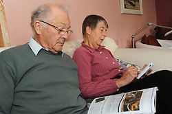 A retired couple enjoy their leisure time, reading and doing brain exercises on the Nintendo DS together,Cumbria.  Model Released.