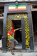 A Cuban Rastafarian rastaman stands outside his doorway, painted in Rasta colours, Havana old town.