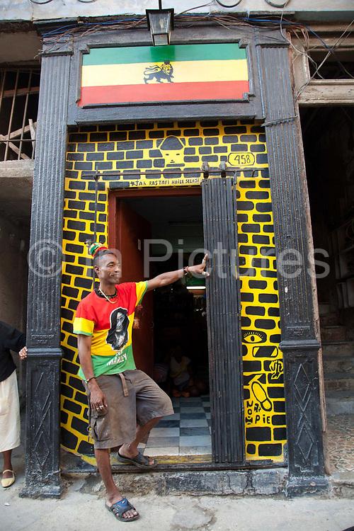 A Cuban Rastafarian rastaman stands outside his doorway, painted in Rasta colours, Havana old town.