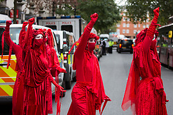 London, UK. 4th September, 2020. Extinction Rebellion's Red Rebel Brigade attend a protest outside the Department for Transport by activists from HS2 Rebellion. Activists glued themselves to the doors and pavement outside the building and sprayed fake blood around the entrance during a protest which coincided with an announcement by HS2 Ltd that construction of the controversial £106bn high-speed rail link will now commence.