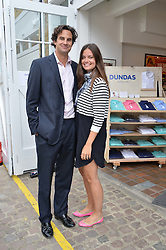 MR RUPERT & LADY NATASHA FINCH at the launch of Dundas London held at Fiskins Classic Car Showroom, 14 Queens Gate Place Mews, London on 25th June 2014.