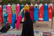 A local woman walks past colourful dress designs on a stall at the weekly market at Qurna, a village on the West Bank of Luxor, Nile Valley, Egypt. The latest in patterns for the modern Egyptian woman are being sold in a beautiful line of fashions and styles. Amidst the bustle of this busy regular event, people from many miles around have come to trade and buy their provisions.