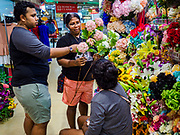 13 DECEMBER 2018 - SINGAPORE:  People buy flowers at a shop in the Joo Chiat complex. Joo Chiat is a multi-tower high rise residential estate. There are hawker food stalls and retail businesses on the ground floor and residences on the upper levels.  The Geylang area of Singapore, between the Central Business District and Changi Airport, was originally coconut plantations and Malay villages. During Singapore's boom the coconut plantations and other farms were pushed out and now the area is a working class community of Malay, Indian and Chinese people. In the 2000s, developers started gentrifying Geylang and new housing estate developments were built.      PHOTO BY JACK KURTZ
