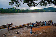 """As a bus stop, boats waits for passengers at the Imaza amazonic rivert-port. After the events of June 5 in the Amazonian province of Bagua, in northeastern Peru, where 24 policemen and a number still not confirmed of natives from the communities of the ÒAlto Mara-onÓ and civilians died in clashes after a series of demonstrations in opposition to the approval by the Peruvian government, for a group of ordinances that allow large flexibility in the restrictions on resource extraction in the area, breaking the 169 agreement of ILO (International Labour Organization), which requires the consultation of indigenous communities about the exploitation of nature in their territories. One of the most active communities was the awajun, a warlike and revengeful people, heritors of the Jibaros and recently contacted near to 1950. For the leader or """"apu"""" for one of the aguarunas riverside communities of the Mara-on, Simon Weepiu, Òthe force of this movement come from the conviction of the struggle, which is caused by the ancestral development as based on worldview, which provides the native of a special power, that of becoming one with his idea and his brothers, to focus all on the same objective and be just a great strength."""" The government aims to generate development in the area allowing the exploitation of property, The jungle is rich in gold and oil, and even argue that natural wealth of the region belong to all Peruvians, and not just the communities that inhabit it, but acts as the oil«s filtration to waters of the Mara-on, left in evidence that in a complex ecosystem like jungle that mixed spilled oil by rain in the river, home to fishes, as well as the waters that irrigate cassava, bananas, sugarcane and other elements vital to the development of communities. The natives, insist that the forest is not only home, is where they get medicines to cure their sick and food for their families. The pre-existence and natural wisdom places them in a privileged place in defining or"""