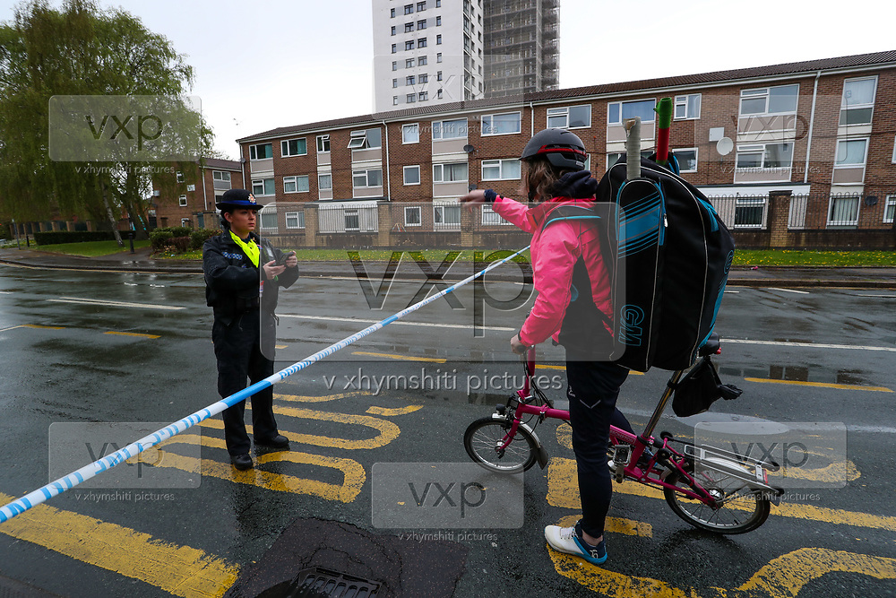 Greater Manchester Police officer (L) talks to a resident (R) who'd like to return home while Bomb Disposal Units are at the scene in Old Trafford, Manchester on Thursday, April 29, 2021, following an allegation over an explosive device. (Photo/ Vudi Xhymshiti)