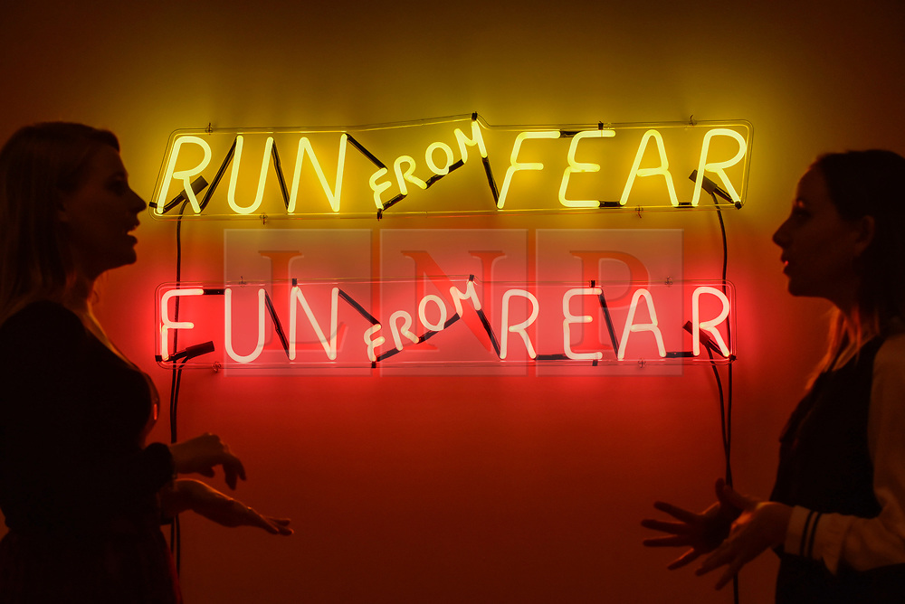 """© Licensed to London News Pictures. 31/07/2017. London, UK. Gallery staff in front of a neon work called """"Run From Fear, Fun From Rear"""", 1972, by Bruce Nauman.  Preview of the new Artist Rooms exhibition of Bruce Nauman at Tate Modern on currently until July 2018.  Nauman is widely regarded as one of the most innovative and influential American artists working today.  The Artist Rooms gallery is the London hub for showcasing work from the Artist Rooms collection which is owned jointly by Tate and the National Galleries of Scotland.  Photo credit : Stephen Chung/LNP"""