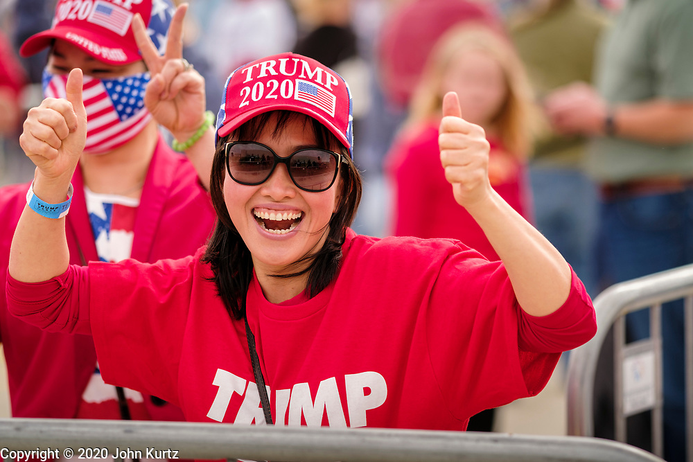 14 OCTOBER 2020 - DES MOINES, IOWA: A woman cheers for President Donald Trump before a Trump reelection rally in Des Moines. About10,000 people were expected at the Des Moines International Airport for a campaign rally supporting the reelection of President Donald Trump. Trump spoke at the rally, despite testing positive for COVID-19 less than three weeks ago. The rally did not meet the CDC guidelines for a safe gathering in the time of Coronavirus and violated Iowa's health emergency declarations barring gatherings of more than 25 people. This week Iowa exceeded 101,000 cases of COVID-19 and a surge in hospitalizations for COVID-19.       PHOTO BY JACK KURTZ