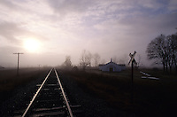 railroad tracks running by a country church and along a road in Southern Arkansas on a foggy morning