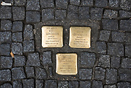 """Berlin, Germany - September 3, 2015: Three brass brick plaques on a Berlin sidewalk mark the location of the former home of Gerda, Ilse, and Arthur Dannenbaum, who were deported and died in the Holocaust. Similar plaques are found throughout Berlin and other cities. The plaque is called a stolperstein (literally """"stumbling block"""") and commemorates victims of Nazi oppression."""