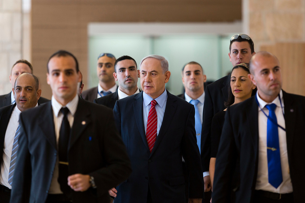 Surrounded by bodyguards, Israeli Prime Minister Benjamin Netanyahu (C) arrives to a Likud faction meeting at the Knesset, Israel's parliament in Jerusalem, on December 3, 2014. Israeli legislators voted Wednesday to dissolve the parliament, and they set March 17 as the date for parliamentary elections, two years ahead of schedule, following a crisis within Prime Minister Netanyahu's coalition government.