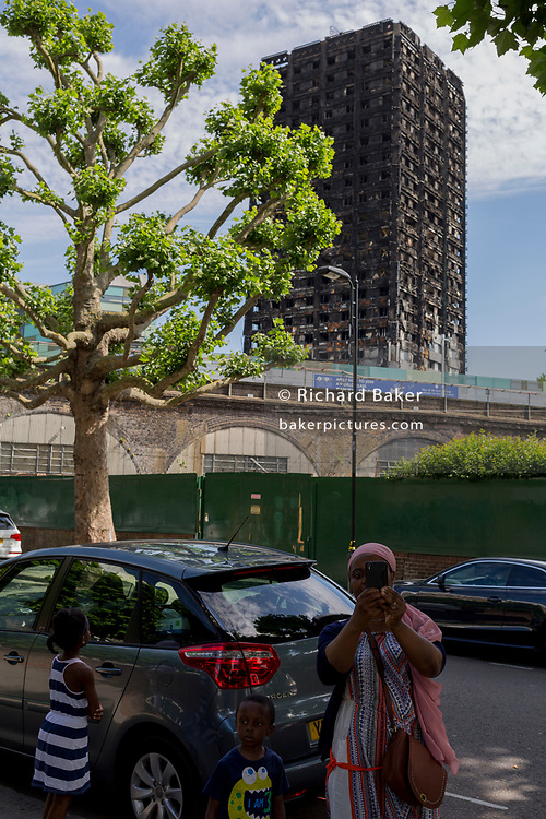 Twelve days after the devastating fire that killed an unspecified number of people in Grenfell Tower, a passer-by pauses to take a selfie with children of the charred and blackened tower block which remains a crime scene, on 26th June 2017, in the London borough of Kensington & Chelsea, England.